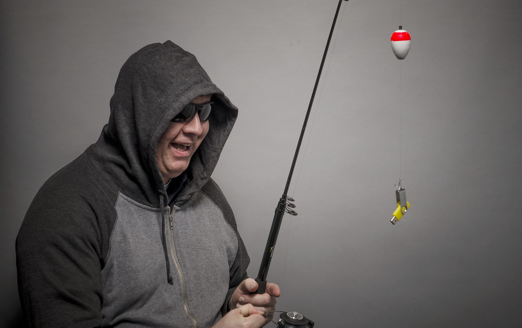 A hooded middle aged white man wearing sunglasses laughs as he holds a fishing pole with a USB drive at the end of the line.