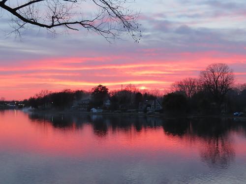 michigan whitmorelake lake sunset sky clouds tree red halo black water reflection
