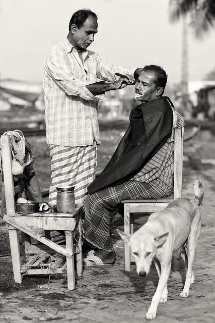 Bangladesh, open air hair salon with dog