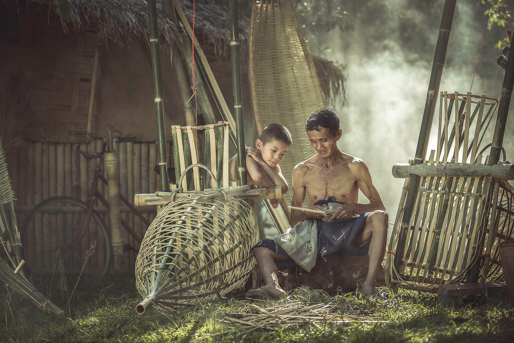 Asian Old man and boy in rural areas are woven bamboo.