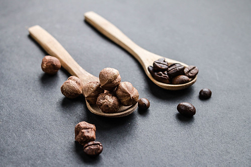 Hazelnuts and coffe beans in wooden spoons | by wuestenigel