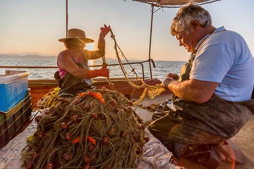 sea fish man net sunrise boat fishing fisherman aegean oldman fishnet greece captain gr arkadia peloponnese fisherwoman