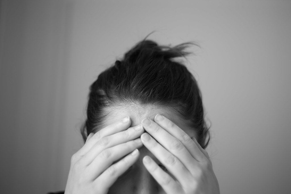 Black and white image of woman with hands on forehead in discomfort.