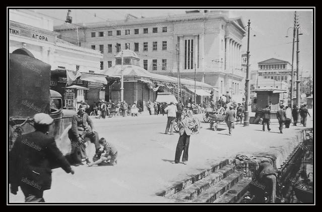Το λιμάνι του Πειραιά κατά την διάρκεια της γερμανικής κατοχής. Διακρίνονται από αριστερά: ένα μέρος της Δημοτικής Αγοράς, το Μέγαρο της Εθνικής τράπεζας (Μέγαρο ΝΑΤ), το καμπαναριό της Αγίας Τριάδας και τέλος η πίσω πλευρά του Δημοτικού Θεάτρου.