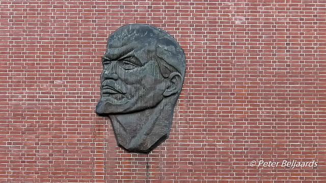 Sculpture of Vladimir Lenin on a brick wall Behrenstraße Berlin Germany.