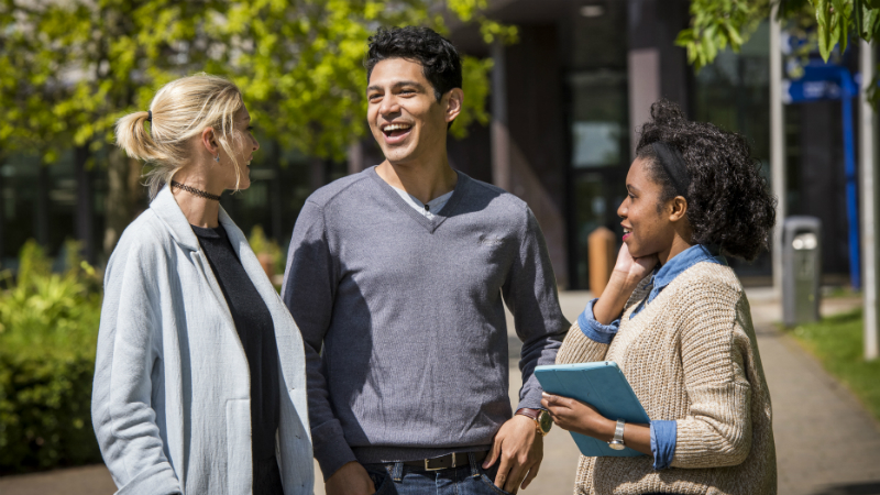 Three students talking on campus