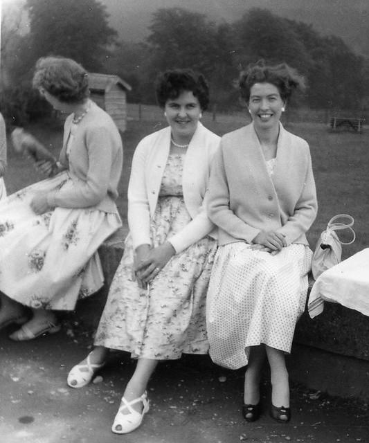Stylish 50s ladies sat on a wall