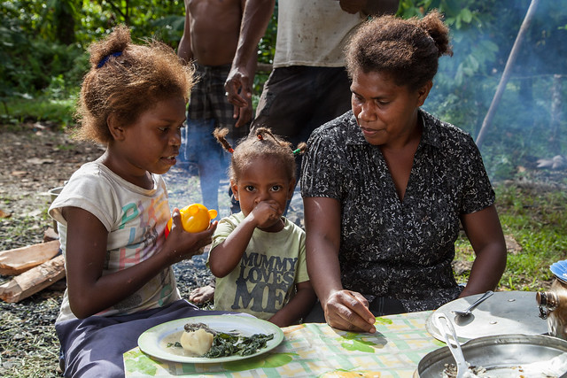 A mother and her daughters share a meal of Mozambique tilapia, cabbage and potato with coconut milk, Taflankwasa village, Malaita Province, Solomon Islands. Photo by Filip Milovac.