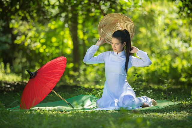 Pretty girl in Vietnam, sitting on a mat with a red umbrella.
