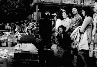 Japanese-Canadian internees wait for a train to take them to ships headed for Japan... / Canadiens d'origine japonaise d'un camp d'internement qui attendent un train pour se rendre à des navires en partance pour le Japon...