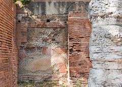 Brick walls (opus testaceum) on the sides; front-facing wall of opus mixtum (bands of brick and tufa), with lateral 'toothing' and a structural arch; plus rough-hewn travertine column--Portico of Claudius, Portus (c. 50 AD)