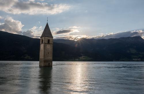 italy italia südtirol mountain steeple lake reschensee lagodiresia water sunset sky sunstar church