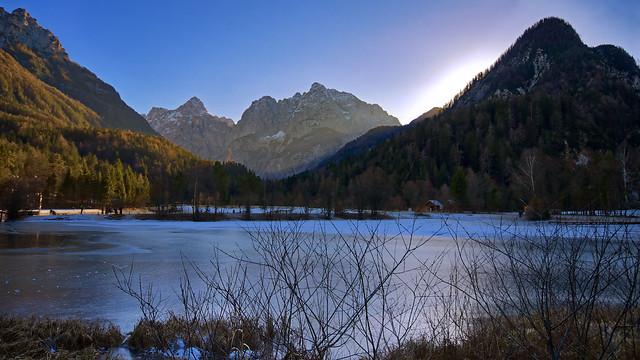 Alpine peaks and frozen lake in Slovenia.
