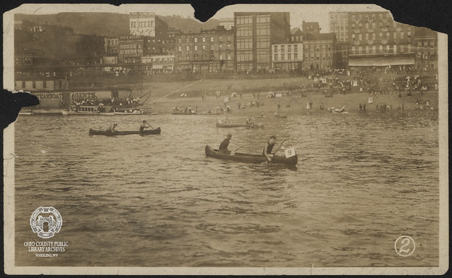 Canoe Race Past the Wheeling Wharf