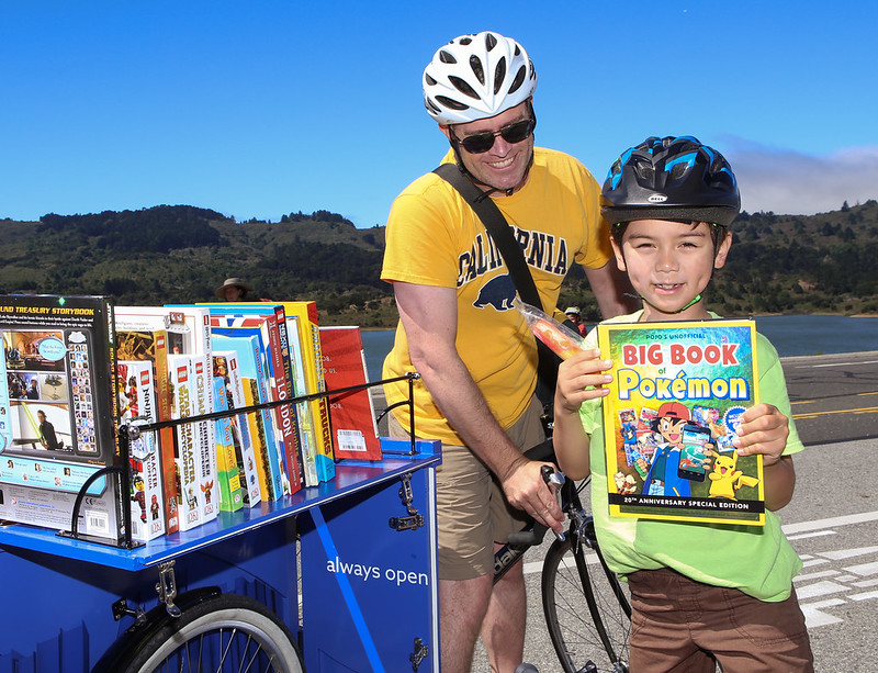 Child grabbing a book from one of our Book Bikes.
