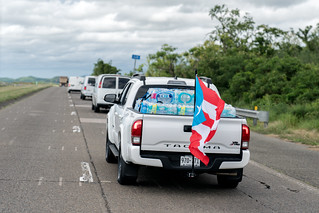 Truck with a Puerto Rican flag carrying water on the highway