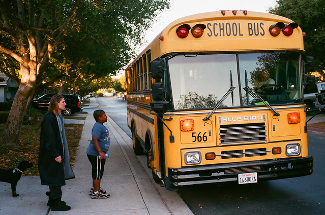 Children board a school bus as parents say good-bye