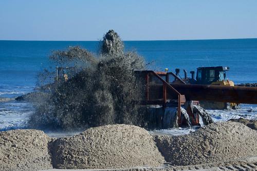 Photo of equipment blasting sand onto a beach