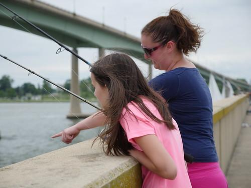 Photo of woman and daughter fishing from a bridge