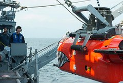 In this file photo, Mineman 1st Class Justin Crabtree lowers a mine neutralization vehicle into the water from USS Chief (MCM 14) during a previous exercise with the JMSDF. (U.S. Navy/MC2 Jordan Crouch)