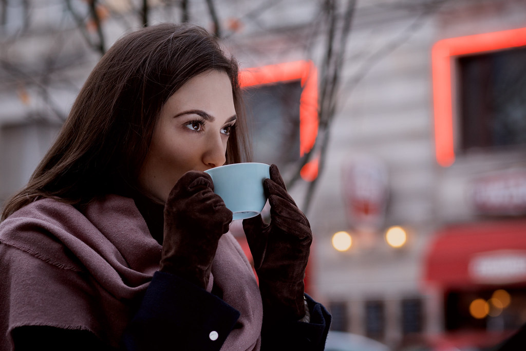 A woman drinking coffee outdoors