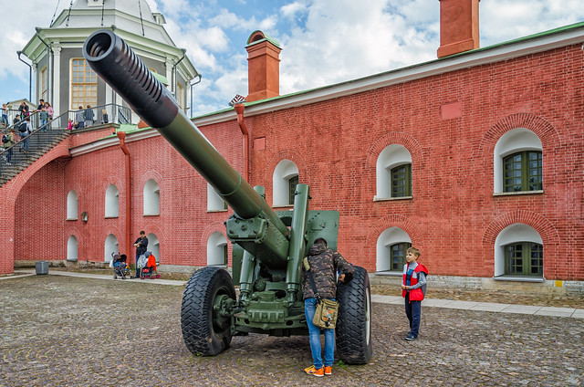 Saint Petersburg, Russia, June 12, 2015. St. Peter and Paul fortress. Father and boy studying the weapon of the World War II at the walls of the fortress by the Flag tower.