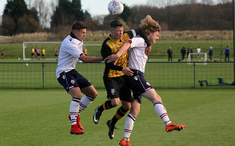 Alex Hunt fights an aerial duel with Bolton pair Dennis Politic (left) and Luca Connell (right)