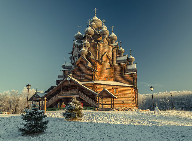 Russia, Saint Petersburg suburbs. A winter view of the of Pokrovskaya church and two little firs at Bogoslovka manor in the Christmas time.