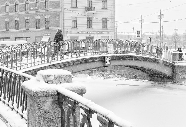 The strong snowstorm in Saint Petersburg. People walking along Sennoy bridge.  B/w image.