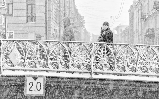 The strong snowstorm in Saint Petersburg. People walking along Demidov bridge.  B/w image.