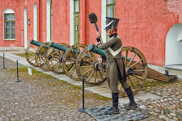 Saint Petersburg, Russia, June 12, 2015. The old bronze cannons in the inner yard of the St. Peter and Paul fortress and the gunner mannequin.