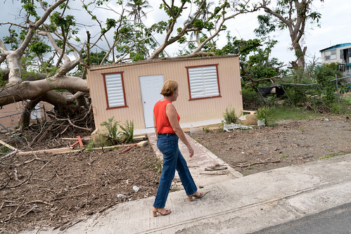Julia Nazario Fuentes, Mayor of Loiza walking past damaged house in Loíza, Puerto Rico | by Lorie Shaull
