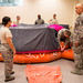 1st Sgt. David Brown, of the 459th Operations Services Squadron, who flies with the Flying Circus Aerodrome and Airshow in Bealeton, Va., talks with Airmen inspecting a life raft at Joint Base Andrews, Md., Aug. 5, 2017. (U.S. Air Force photo by J.M. Eddins Jr.)