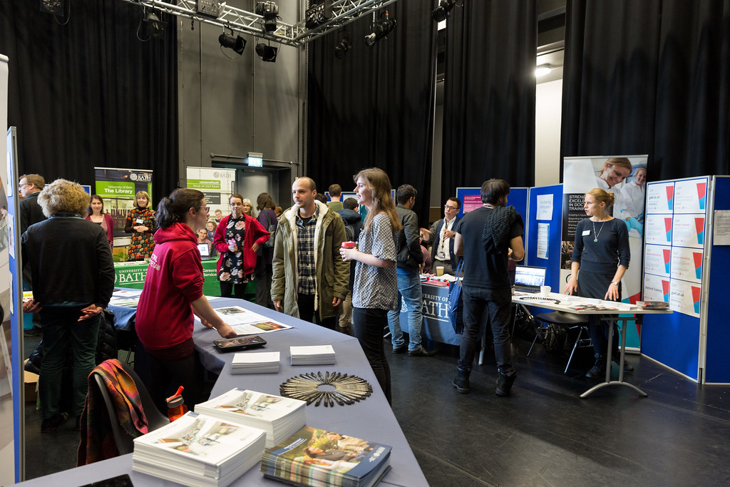 Attendees interacting with exhibitors and a previous information fair