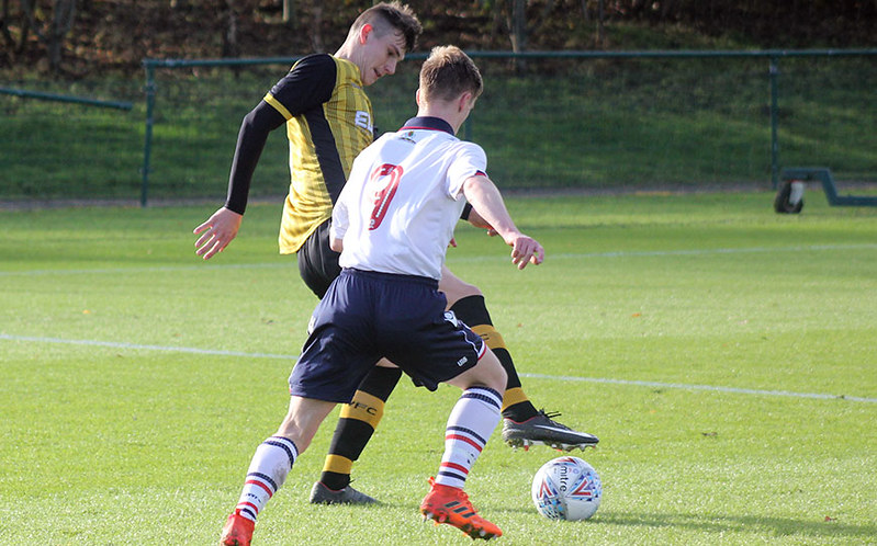 Wednesday's Liam Shaw attempts to shield the ball from Matthew Argent-Barnes