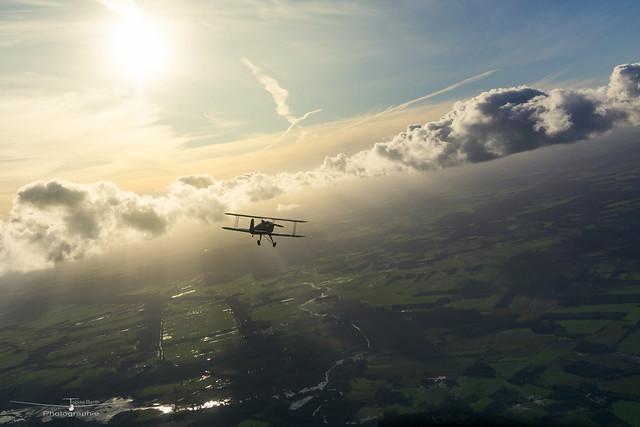 Biplane between the clouds