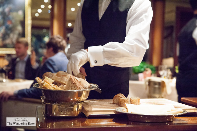Bread service with waiter slicing the bread tableside