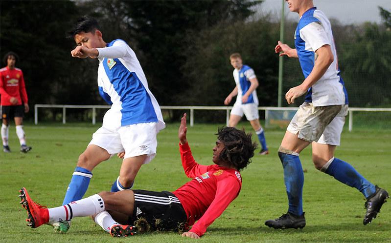 Tahith Chong slides in to challenge Matthew Chang