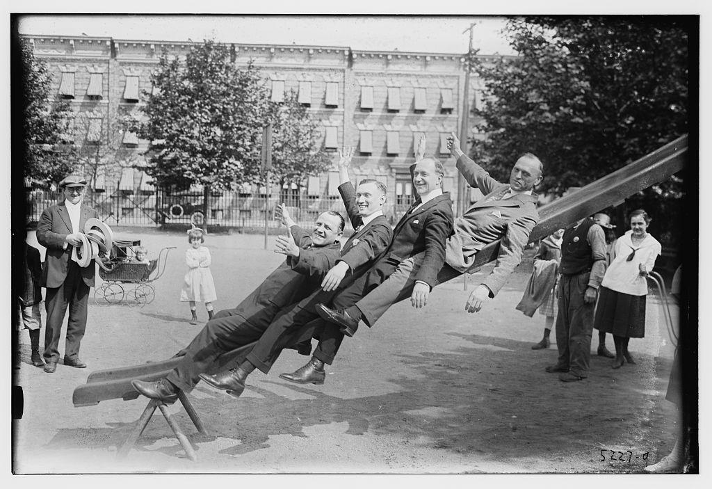 4 men on slide in park (LOC)