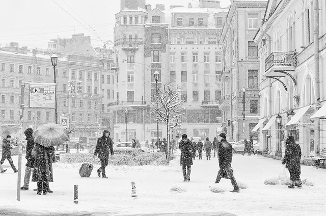 The strong snowstorm in Saint Petersburg. People walking around Sennaya square.  B/w image.