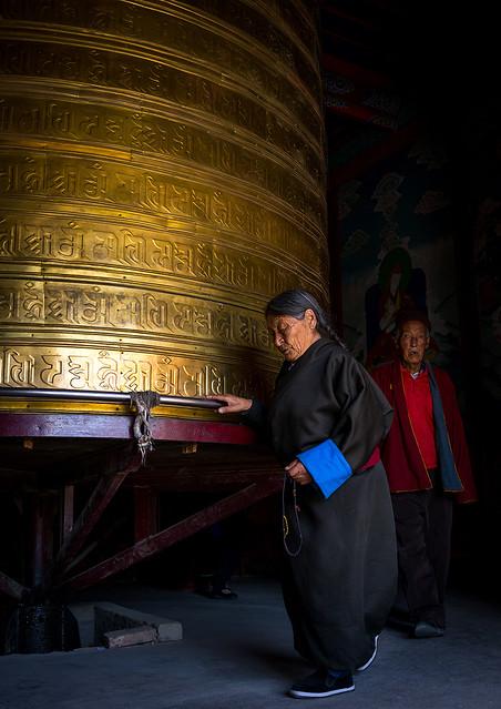 Tibetan pilgrims turning huge prayer wheel in Rongwo monastery, Tongren County, Longwu, China