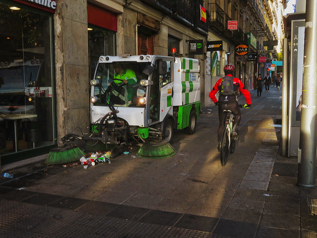 street cleaner and cyclist on sidewalk, morning; Madrid (2017)
