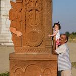 Grandfather showing child khachkar in Shushi