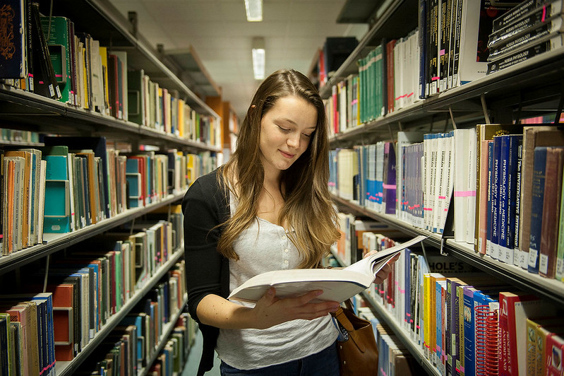 Female student in a library reading a book