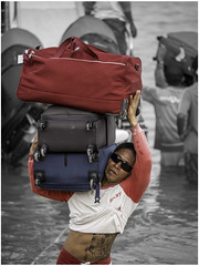 A sailor of a fastboat ferry carries suitcases to the shore
