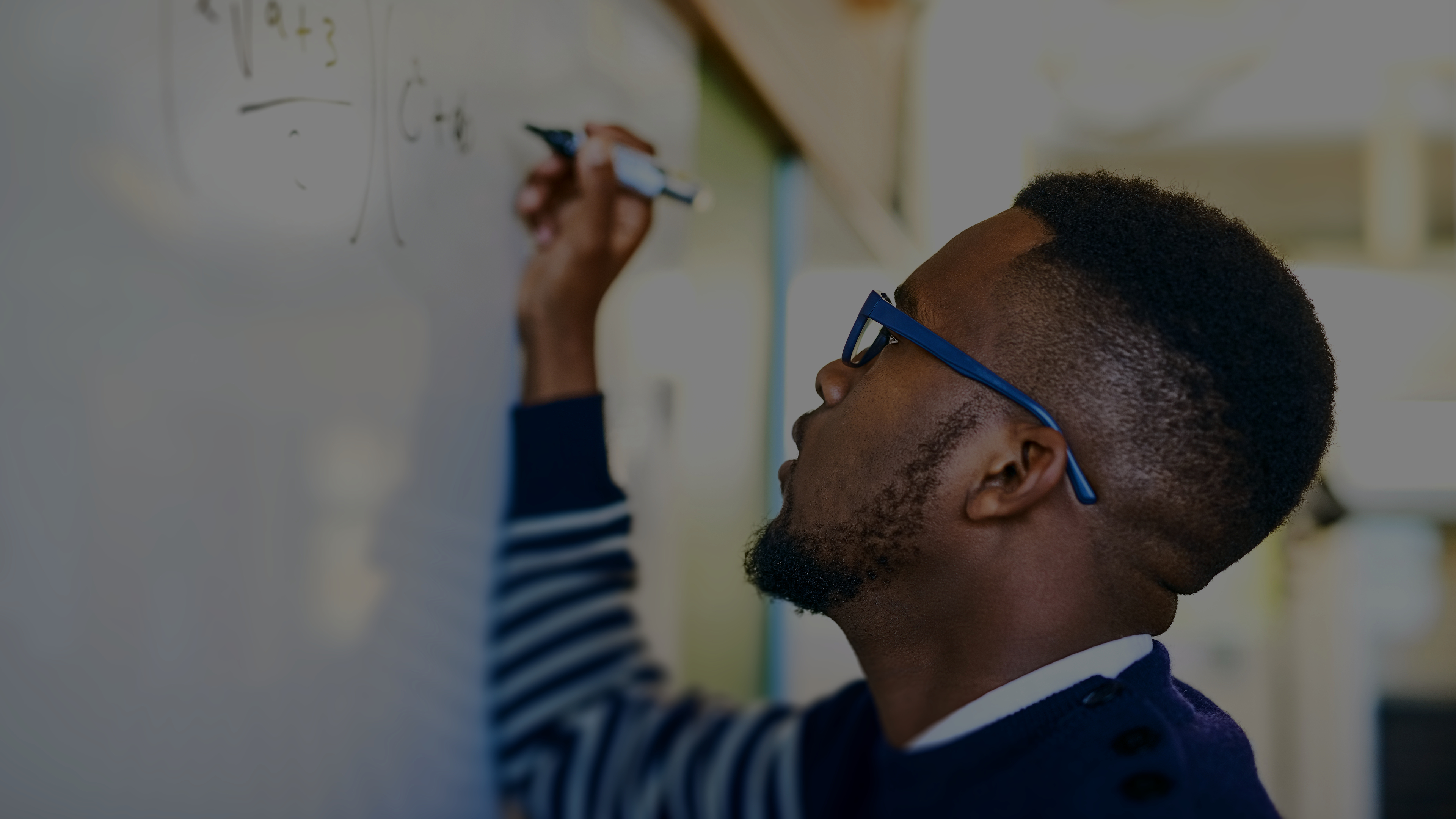 Photo of a student writing mathematical equations on a whiteboard.
