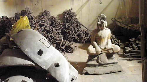 A broken Buddha meditates amongst the leg irons in the Genocide Museum, formerly the S-21 Prison, in Phnom Penh, Cambodia