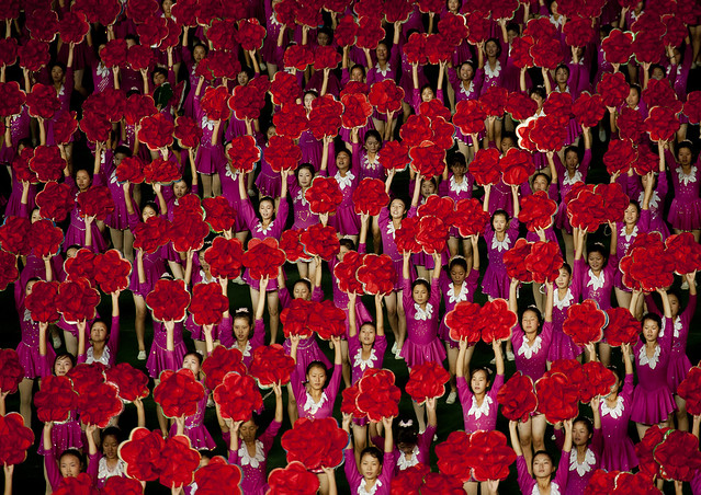 North Korean gymnasts holiding red flowers during Arirang mass games in may day stadium, Pyongan Province, Pyongyang, North Korea