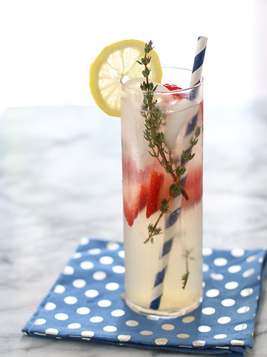 strawberry thyme lemonade with straw in a tall glass on polka dot napkin | by Berries.com