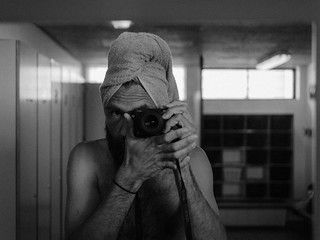 Mirror self portrait by a man with a camera and a towel on his head.
